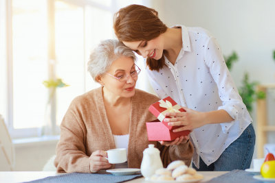 adult daughter gives gift and congratulates an elderly mother