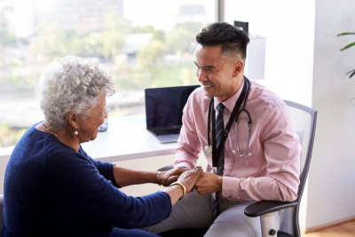 Male Doctor In Office Reassuring Senior Female Patient