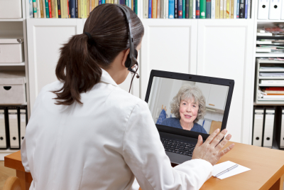 Female doctor with headset in front of her laptop talking via video call